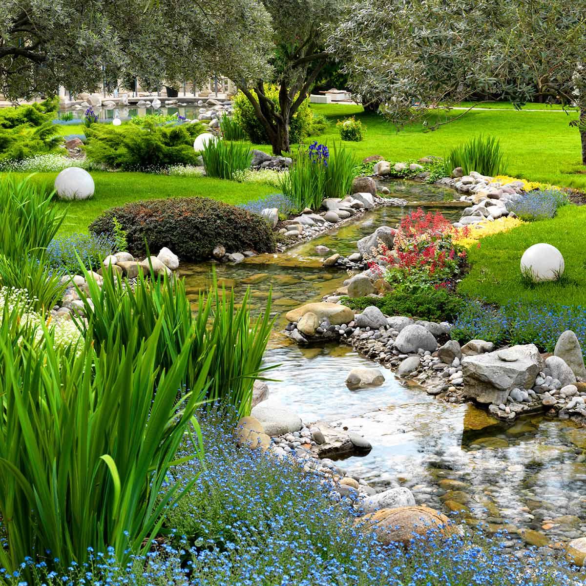 Szeroki strumień, wyłożony kamieniami i otoczakami płynący przez trawnik w ogrodzie w otoczeniu rabat kwiatowych
